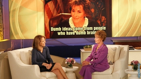 Judge Judy wears a purple pantsuit designed by Susanna Beverly Hills